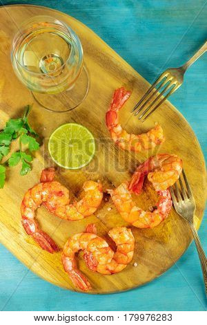 An overhead photo of a glass of white wine with cooked shrimps, a slice of lime, cilantro leaves, salt flakes, and a place for text, on a vibrant blue background