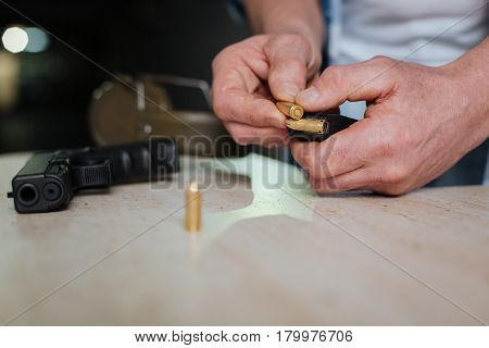 Handgun cartridge clip. Metal handgun bullet being in hands of a man while being put into the cartridge clip