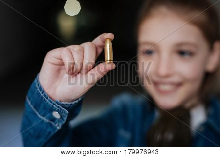 Feeling exited. Selective focus of a handgun bullet being held by a positive delighted cute girl while having a shooting lesson
