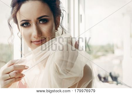 Beautiful Emotional Bride In Sexy Red Robe With White Wedding Veil Portrait Near Window, Morning Bef