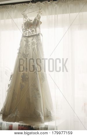 Beautiful White Wedding Dress Hanging Near A Window In Hotel Room, Morning Wedding Preparation, Whit