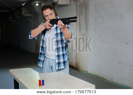 I see the target. Nice handsome pleasant man holding a gun and looking at the target while aiming