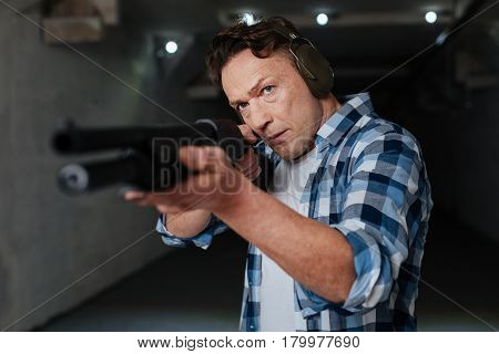 Staying calm. Nice confident handsome man choosing the aim and preparing to shoot while holding a rifle