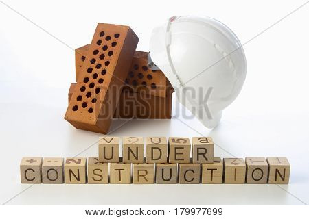 under construction text on wooden cubes on white background