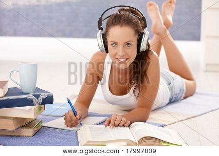 Hübsches Mädchen zu Hause Handauflegen Stock, lernen die Verwendung von Kopfhörern, lächelnd.?