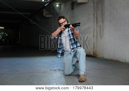 Shooting practice. Nice skilled pleasant man standing on one knee and holding a rifle while training to shoot