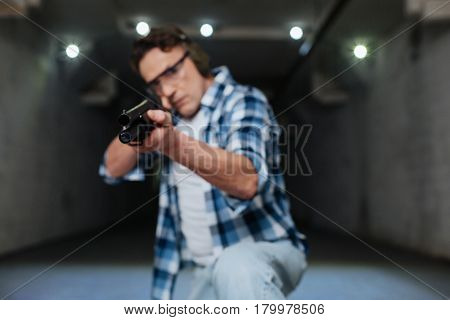 Being a target. Serious skilled nice marksman looking at you and holding a gun while preparing to shoot
