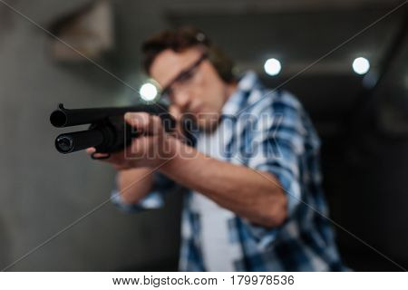 Military weapon. Selective focus of a rifle being in hands of a handsome pleasant good looking man while shooting