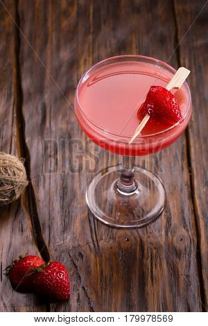 Cocktail from gin with strawberry in a glass with a strawberry piece on a skewer