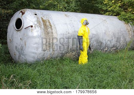 technician in uniform at  large old stainless tank