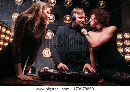 Two young attractive girls flirting with handsome bearded disk jockey at nightclub party. Dance, music, cool party, flirt, coquetry.