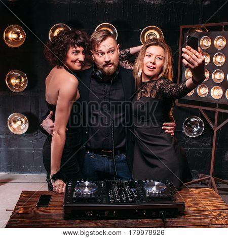 Two adult sexy girls in black dresses and handsome bearded disk jockey making selfie with smartphone at the DJ console. Clubbing, relaxing and fun, party, nightlife.