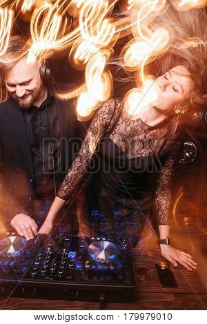 Attractive young girl dancing with bearded disk jockey in headphones at DJ console. Clubbing, party, music, nightlife and fun, light long exposure.