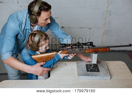 At the shooting range. Mice delighted pleasant man standing behind his daughter and helping her to shoot while having a lesson with her