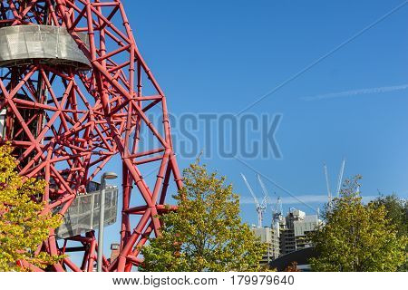 London England - October 17, 2016; From Queen Elizabeth Olympic Park in Stratford London abstract ArcelorMittal Orbit red tubular spiralling steel structure on one side of image with white construction cranes in ditstant city skyline.