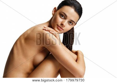 Beautiful naked fashion model with perfect body on white background. Photo of woman sitting on the floor touch legs. Beauty & Skin care concept