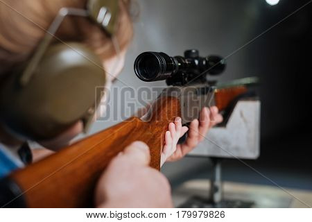 Developing accuracy. Confident pretty skilled girl wearing headphones and looking into the optical sight while shooting at the target