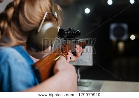 Future markswoman. Nice pleasant serious girl holding a gun and looking at the target while developing her shooting skills