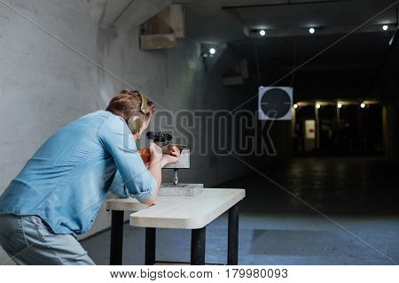 Shooting practice. Handsome confident nice man leaning on the table and directing his gun while trying to hit the target