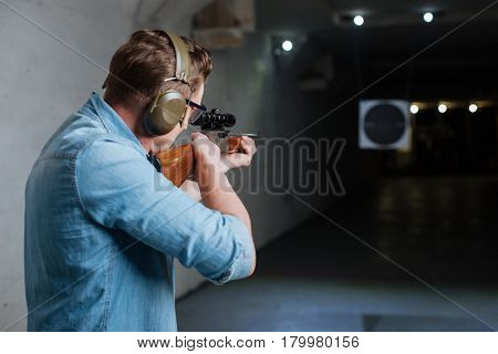 Hitting the bulls eye. Handsome confident serious man holding the rifle and looking into the target while trying to hit the bulls eye