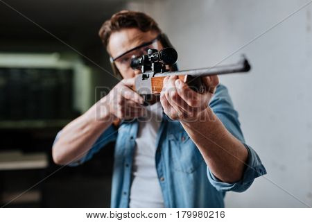 My hobby. Nice pleasant confident man visiting a shooting gallery and aiming with a gun while developing his skills