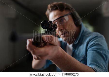 Professional shooter. Handsome professional male sniper holding a gun and looking into the optical sight while choosing the target