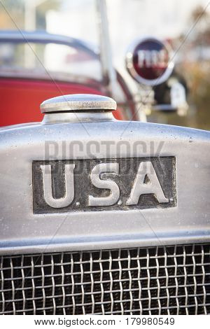 USA on the front radiator grill of an old antique red fire truck.