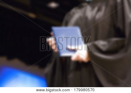 A graduate in a black robe holding a diploma, bokeh, diffused focus effect.