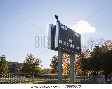 Scoreboard at a fenced in little league baseball field in the afternoon.