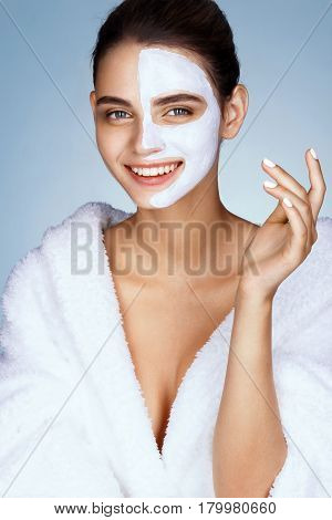 Smiling young girl with cosmetic mask on her face. Photo of beautiful brunette girl wearing white bathrobe. Wellness and Spa concept