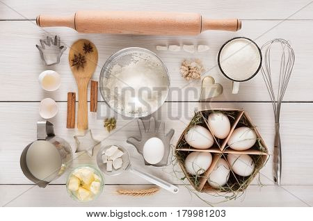 Flat lay Baking background. Top view of cooking ingredients and utencils for yeast dough and pastry on white rustic wood