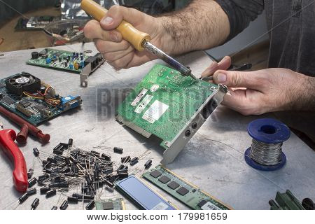 Repair of computer hardware. Modem repair. Replacement of the capacitor.An employee at an electric service while at work. Hand of a soldering soldier with soldering iron.