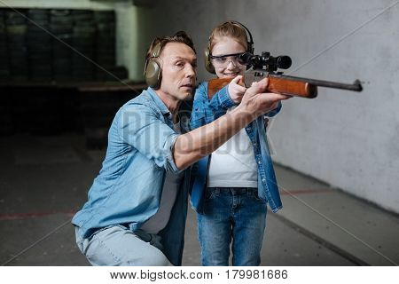Pleasurable activity. Happy delighted nice girl wearing protective glasses and holding a rifle while looking into its optical sight
