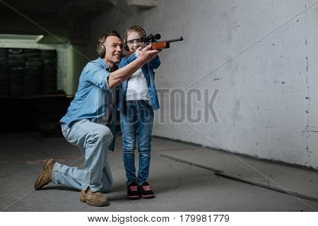 Useful lesson. Good looking joyful positive girl standing with her father and holding a gun while learning how to shoot