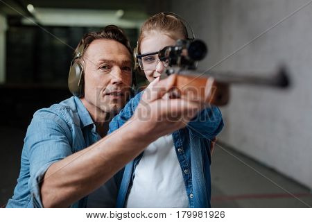 Thinking about safety. Cheerful cute exited girl holding a rifle and looking into its optical sight while wearing protective glasses