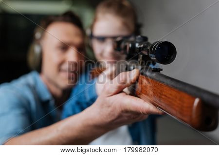 Being accurate. Selective focus of a professional gun with an optical sight being in hands of a young cute girl