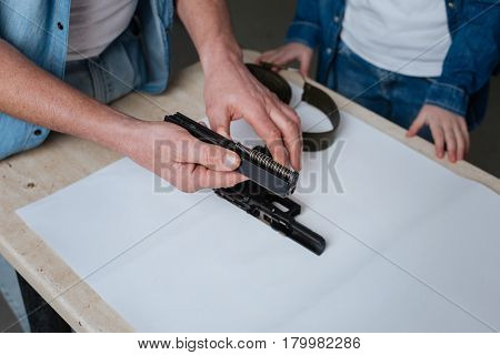 Disassembled handgun. Close up of a handgun detail being in hands of a nice pleasant good looking man while showing it to his daughter