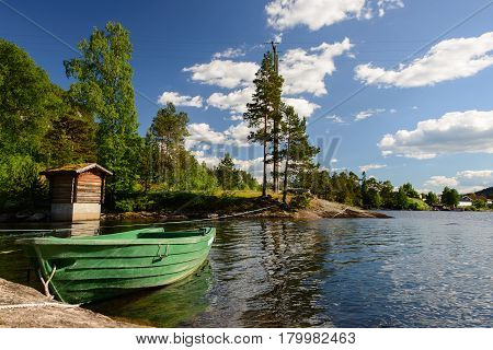 A landscape with a green rowboat in the water under some trees at the border of the fjord in Norway.