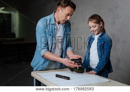 Inner construction. Pleasant nice handsome man holding the disassembled gun and looking at it while showing it to his daughter