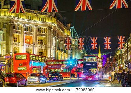 London, United Kingdom - June 18, 2016: Street scene by Oxford street by night, with flags and Londodn bus