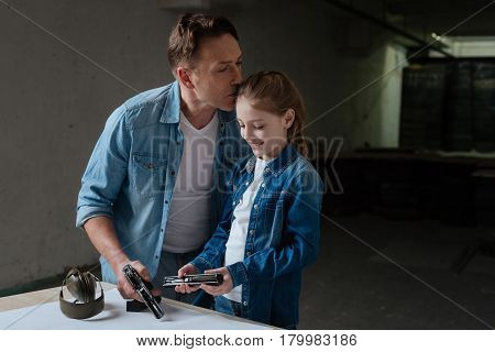 Loving father. Pleasant delighted caring father standing near his daughter and kissing her while expressing his love