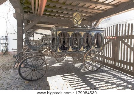 Kaiserslautern Germany - April 18 2015: Theodor-Zink-Museum Garden inside the museum with old carriage used as a hearse. The house is plastered and painted white very bright