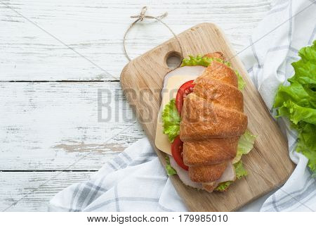 Croissant sandwich with bacon cheese lettuce and tomato on white wooden table. Healthy snack. Top view copy space.