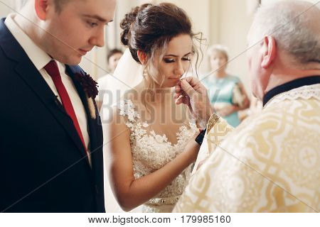 Sensual Happy Groom Kissing Wedding Ring During Wedding Ceremony In Christian Catholic Church, Pries