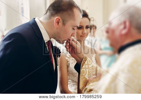 Sensual Happy Bride Kissing Wedding Ring During Wedding Ceremony In Christian Catholic Church, Pries