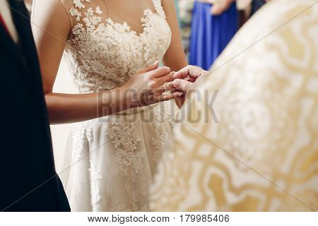 Bride And Groom Exchanging Golden Wedding Rings At Wedding Ceremony In Christian Church, Priest Putt