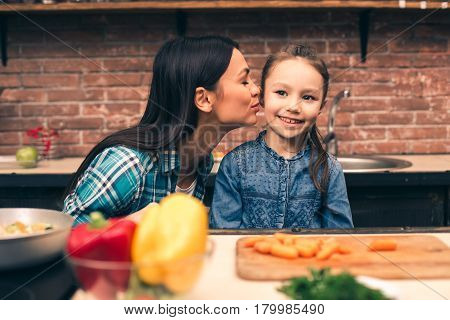 Time to cook together. Photo of mother and little daughter. Woman teaching girl how to cook. Table full of organic vegetables. Woman kissing her daughter