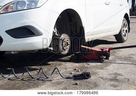 Car without wheel and lift up by hydraulic waiting for tire replacement.