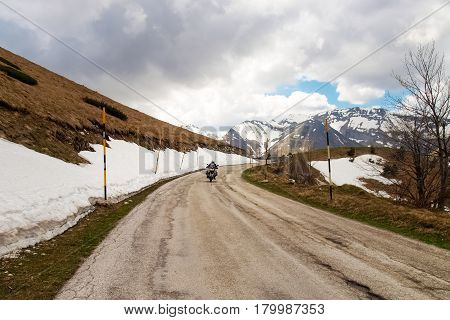 Italy Apennines Umbria-Marche-Abruzzo - April 24 2015: Road Trebbio Bolognola Sarnano. Panorama of the mountains Sibillini. Motorbike is going on the road during the photo shoot.