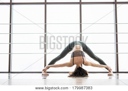 Prasarita Podattanasana. Beautiful Yoga Woman Practice Near Window Yoga Room Studio Background. Yoga